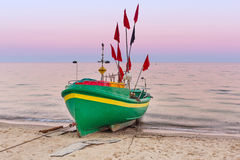 Baltic beach with fishing boat at sunset Royalty Free Stock Photos