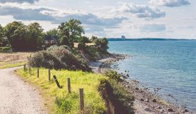 Baltic coastline. Escarpment slope lead to pebble beach. People walking along the shore hanseatic City of Luebeck -. Travemuende, Germany royalty free stock photos