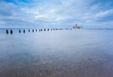 Baltic rocky coast with old military buildings from world war II and wooden breakwaters. Stock Photography