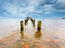Baltic rocky coast with old military buildings from world war II and wooden breakwaters. Royalty Free Stock Photo