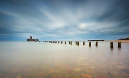 Baltic rocky coast with old military buildings from world war II and wooden breakwaters. Stock Photo