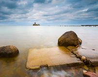 Baltic rocky coast with old military buildings from world war II and wooden breakwaters. Royalty Free Stock Image