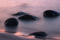 Baltic Sea beach  with stones in sunset Stock Images