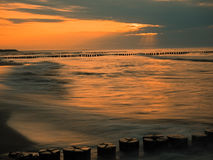 Baltic Sea with breakwaters at sunset.  Stock Images