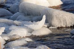 Frozen, icy Baltic Sea coast 18. Baltic Sea coast covered with a lot of shining ice cubes like diamonds on the sand and water surface. Waves are frozen in the stock photo