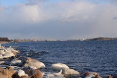 Frozen, icy Baltic Sea coast 14. Baltic Sea coast covered with a lot of shining ice cubes like diamonds on the sand and water surface. Waves are frozen in the royalty free stock photo