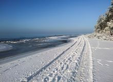 The Baltic Sea coast in snowy winter. Near Liepaja, Latvia. Beautiful frosty clear day with blue sky. Coastal scenery with ice pieces. The road traveled along Stock Images