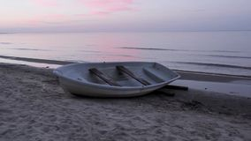 Baltic Sea and a fishing boat. In Melnsils, Latvia in sunrise stock footage