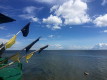 Fishing boat flag poles with blue sea and sky. Baltic sea, a green fishing boat moored on the beach, flag poles pointing at blue cloudy sky Stock Image