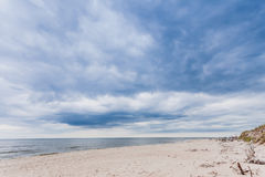 Baltic sea with sandy beach. In the foreground. Water and blue clouds sky in the beckground royalty free stock photos
