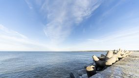 Baltic sea side beach pier. Baltic sea side beach pier in bright sunny day with cold winter winds. Some beautiful scenes of sea side stones royalty free stock image