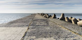 Baltic sea side beach pier. Baltic sea side beach pier in bright sunny day with cold winter winds. Some beautiful scenes of sea side stones stock photo