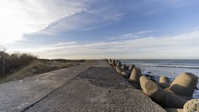 Baltic sea side beach pier. Baltic sea side beach pier in bright sunny day with cold winter winds. Some beautiful scenes of sea side stones stock photos