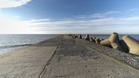 Baltic sea side beach pier. Baltic sea side beach pier in bright sunny day with cold winter winds. Some beautiful scenes of sea side stones royalty free stock photo