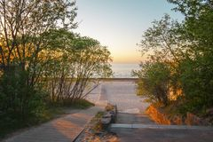 Baltic sea in spring sunset warm light. Sandy beach in Jurmala, Latvia, East Europe. Baltic sea in spring sunset warm light. Landscape with green trees and royalty free stock photography