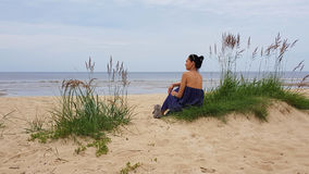 Baltic sea,woman on grassy sand dune with a soft toy Royalty Free Stock Images