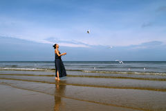Baltic sea,   woman  in summer dress  feeding white gulls Stock Images