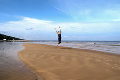 Baltic sea, woman  walking and jumping along the beach Stock Images