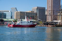 Baltimore Fire Department Boat in the Harbor. Baltimore, MD, USA --April 13, 2019-- A Baltimore City fireboat  sails into the waters of the inner harbor stock photography