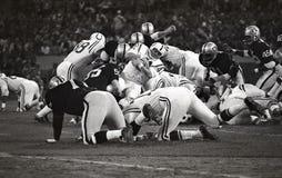 Baltimore hingstfölRB Tom Matte #41 är uppslukad vid Oakland Raidersförsvaret Royaltyfri Foto