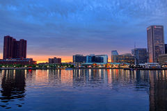 Baltimore Inner Harbor at Dusk. Luxury hotels and restaurants with office buildings and shopping mall over waterfront walk and reflections in the water on the Royalty Free Stock Photography