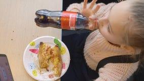 Baltimore, le Maryland, Etats-Unis - 21 février 2019 : coca-cola potable de fille d'adolescent de bouteille dans la pizzeria d'al banque de vidéos