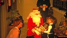 BALTIMORE, MARYLAND 1975: De Kerstman die door voordeur komen om gelukkig kind te bezoeken stock video