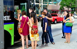 Baltimore, MD: People Boarding MTA Bus. People queue up on Pratt Street to board one of the free MTA Orange Route circulator public transportation buses in Stock Photos
