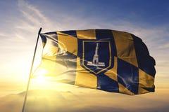 Baltimore-Stadt des Flaggentextilstoffgewebes Vereinigter Staaten, das auf den Spitzensonnenaufgangnebelnebel wellenartig bewegt stockbild