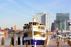 Baltimore, USA - January, 31 2014: Raven is the newest yacht in Watermark fleet. The Inner Harbor during winter with Raven yacht at the dock and Legg Mason royalty free stock images