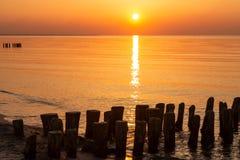 Baltische Küste mit hölzernen Wellenbrechern bei Sonnenuntergang oder Sonnenaufgang Dämmerung in Ostsee stockfotos