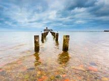 Baltische rotsachtige kust met oude militaire gebouwen van Wereldoorlog II en houten golfbrekers Royalty-vrije Stock Foto