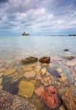 Baltische rotsachtige kust met oude militaire gebouwen van Wereldoorlog II en houten golfbrekers Stock Foto