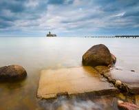 Baltische rotsachtige kust met oude militaire gebouwen van Wereldoorlog II en houten golfbrekers Royalty-vrije Stock Afbeelding
