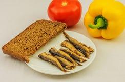 Baltische Sprotten und Brot auf einer Platte, einem gelben Pfeffer und einer Tomate Stockbild