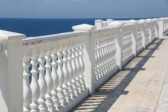 Baluster beach. White columns overlooking the sea. View of white pillars and horizont on blue sea and the sky in the Stock Photography