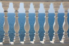 Baluster beach. White columns overlooking the sea. View of white pillars and horizont on blue sea and the sky in the. Background royalty free stock images