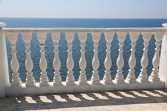 Baluster beach. White columns overlooking the sea. View of white pillars and horizont on blue sea and the sky in the. Background royalty free stock image