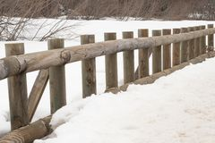 Baluster de madeira da ponte sobre o lago congelado imagem de stock