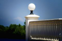 A Baluster with Spherical Lamp. A white baluster with a lamp in front of the forest on the lake royalty free stock images