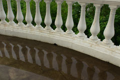Balusters of rounded handrails with reflection in water. Photo royalty free stock photo