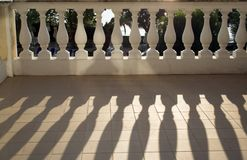Balustrade casting shadows in sunshine. On the balcony floor stock images
