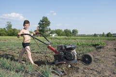 Balza nel giardino un ragazzino che ara la terra il motore-b Fotografia Stock
