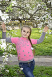 Balza nel giardino una bambina che tiene un ramo della ciliegia. Fotografia Stock