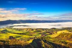 Balze di panorama nebbioso di mattina di Volterra, di terreni coltivabili e del fi verde immagini stock libere da diritti