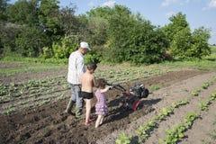 Balzi nell'uomo del giardino che ara figlio del motore-blocco della terra il piccolo e Immagini Stock Libere da Diritti