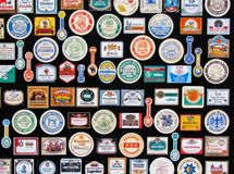Fragment of collection of vintage beer labels set out as decoration in a pub. Beer bottle stickers and coasters isolated on black. Bamberg, Germany - January 4 royalty free stock images