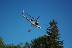 Bambi bucket. Helicopter with bambi bucket on the fire Stock Photography