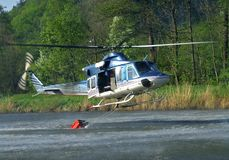 Bambi bucket. Helicopter with bambi-bucket gathering water in a pond Stock Images