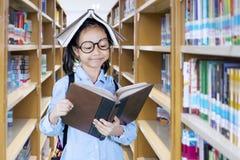 Bambina abile con il libro sopra la sua testa Fotografia Stock